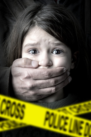 Scared young girl with an adult mans hand covering her mouth photo
