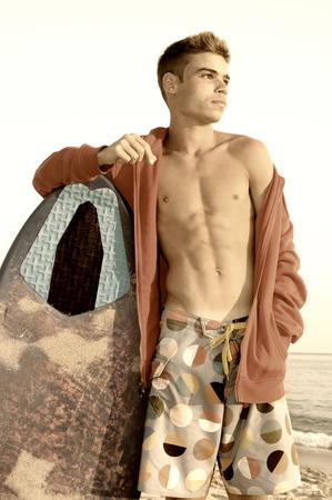 skimming: Adolescente hermoso que presenta en la playa con tabla de desnatado