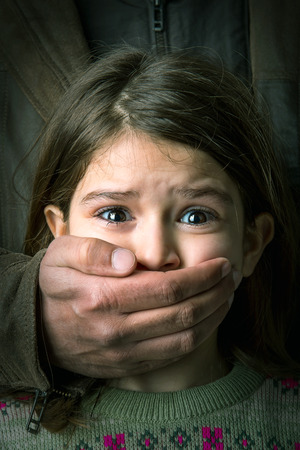 Chica joven asustado con la mano de un hombre adulto que cubre la boca Foto de archivo