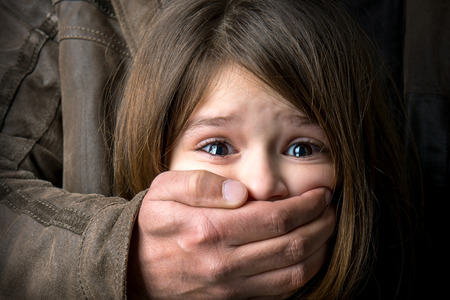 trapped: Scared young girl with an adult mans hand covering her mouth