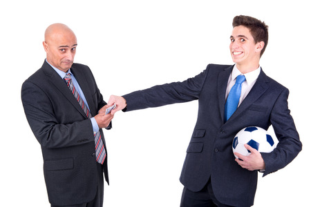 Dispeased businessman paying a lost bet to a happy rival over a football game photo