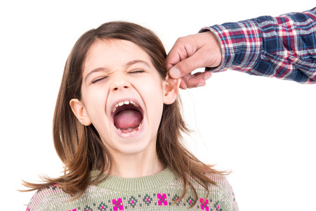 Young girl being punished with ear pulling