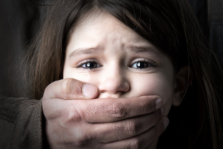 Scared young girl with an adult mans hand covering her mouth