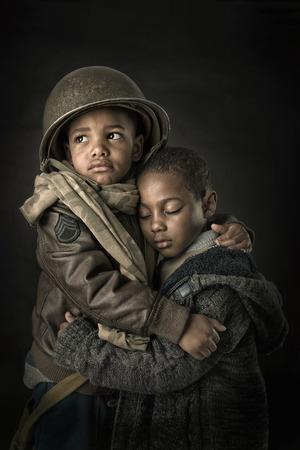 그의 어린 동생을 보호 소년 군인의 극적인 세로 스톡 콘텐츠