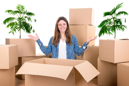 Beautiful girl with cardboard boxes unpacking in new home Stock Photo