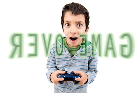 jugando videojuegos: Boy jugando juegos de video que hacen caras aislados en blanco Foto de archivo