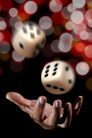 Hand throwing dice in a dark background Stock Photo