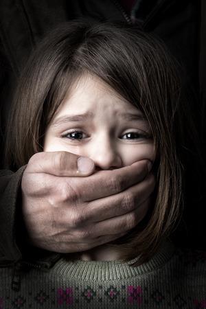 彼女の口を覆っている成人男性の手で若い女の子を怖がっています。 写真素材