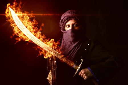 woman warrior: Arabic Woman warrior with sword on fire against a dark background Stock Photo