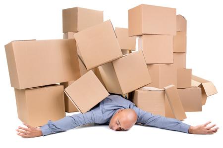 Müde Geschäftsmann unter einem Haufen von Kartons