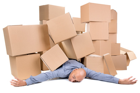 Tired businessman under a pile of cardboard boxes Stockfoto