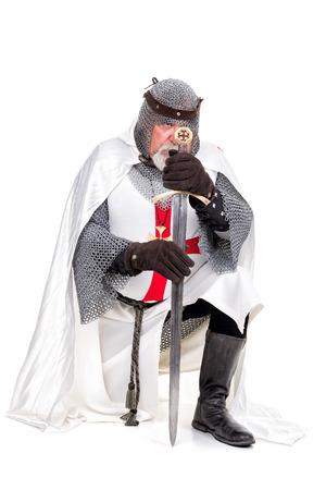 Knight Templar praying isolated in white photo