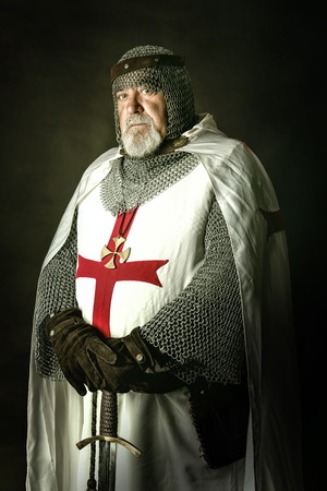 armour: Knight Templar posing with sword in a dark background Stock Photo