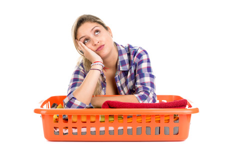 houseclean: Tired young woman doing the laundry at home