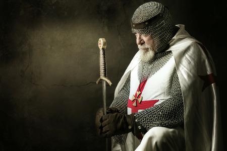 Templar knight praying in a dark background