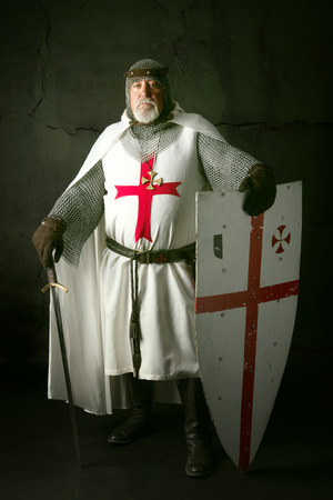 Knight Templar posing with sword in a dark background Archivio Fotografico