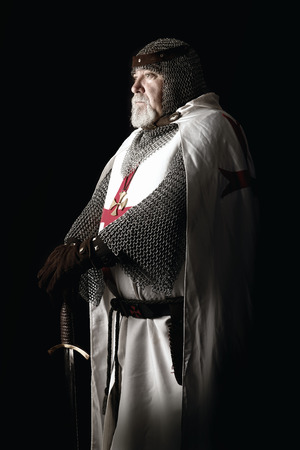 Knight Templar posing with sword in a dark background Stockfoto