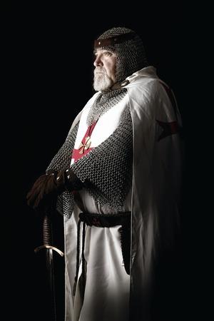Kreuzritter mit Schwert posiert in einem dunklen Hintergrund