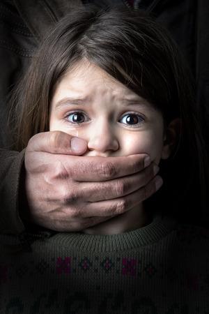 asustado: Chica joven asustado con la mano de un hombre adulto que cubre la boca Foto de archivo