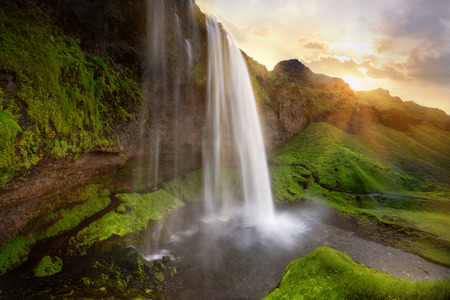Beautiful and dramatic sunset in Seljalandsfoss waterfalls, Iceland Фото со стока