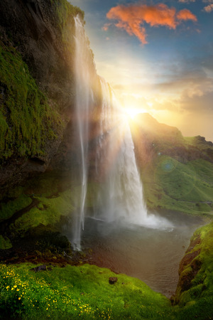 Schöne und dramatischen Sonnenuntergang in Seljalandsfoss Wasserfall, Island Standard-Bild