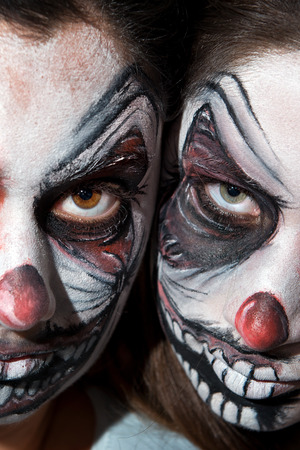 Teenage girls with scary clown face painting