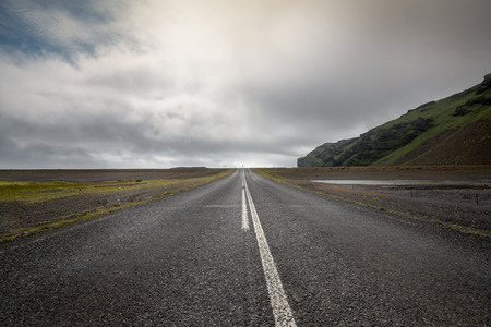 dirt road: Empty road with cloudy skies in wild Iceland
