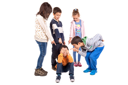 bully: Group of children bullying an isolated child Stock Photo