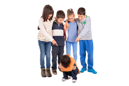 girl kick: Group of children bullying an isolated child Stock Photo