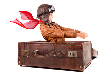 Young boy pilot flying an old suitcase isolated in white