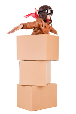 cardboard box: Young boy pilot flying a cardboard box isolated in white
