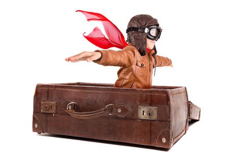若い少年パイロットは、白で隔離された古いスーツケースを飛んで