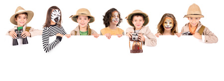 Children's group in safari clothes and face-paint over a white board Stockfoto
