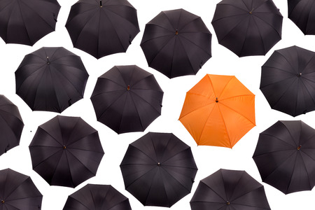 amongst: Orange umbrella amongst black umbrellas viewed from above isolated in white
