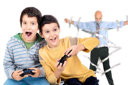 jugando videojuegos: Muchachos que juegan a los videojuegos y padre pegados a la pared con cinta adhesiva en el fondo