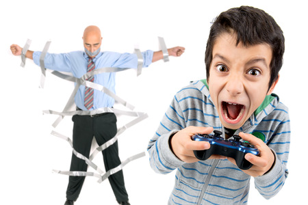 playing video games: Boy playing video games and dad glued to the wall with duct tape in the background