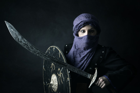 Arabic Woman warrior portrait against a dark background