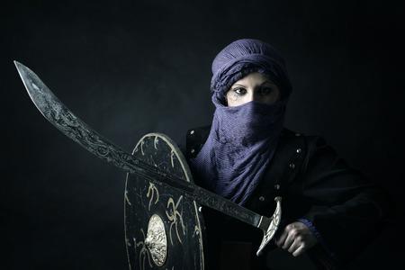 espadas medievales: �rabe Guerrero de la mujer retrato contra un fondo oscuro Foto de archivo