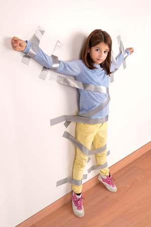 girl tied: Young girl tied to the wall with duct tape