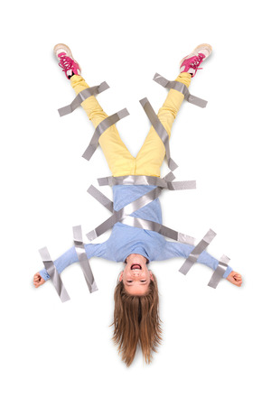restrain: Young girl tied upside down to the wall with duct tape Stock Photo