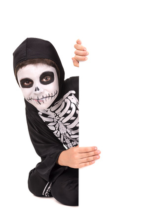 haunt: Boy with face-paint and skeleton Halloween costume over a white board