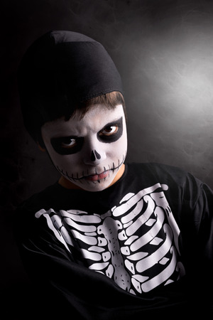 haunt: Boy with face-paint and skeleton Halloween costume isolated in a dark background Stock Photo