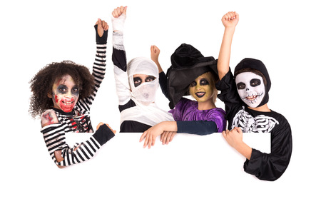 haunt: Kids with face-paint and Halloween costumes over a white board