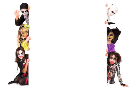 Kids with face-paint and Halloween costumes over a white board