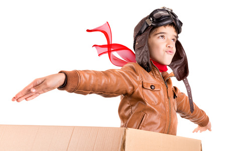 Young boy pilot flying a cardboard box isolated in white