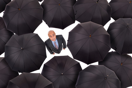amongst: Businessman standing amongst black umbrellas isolated in white