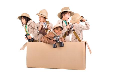 Children's group in a cardboard box playing safari Foto de archivo