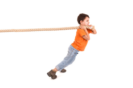 Boy pulling a rope isolated in white Stockfoto