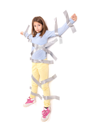 tied girl: Young girl tied to the wall with duct tape