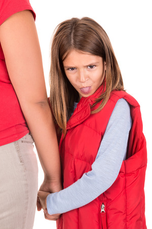 making faces: Young girl making faces and holding her mothers hand Stock Photo